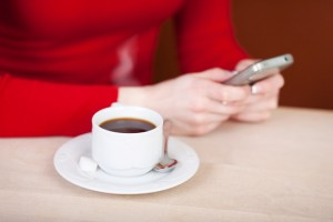 woman writing sms and drinking coffee